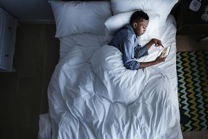 Man in bed using a digital device