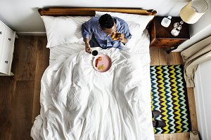 Man in bed having a breakfast in bed