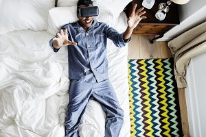 Man in bed using a VR headset