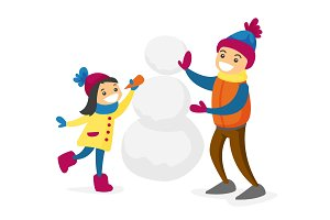 Caucasian white boy and girl building a snowman.