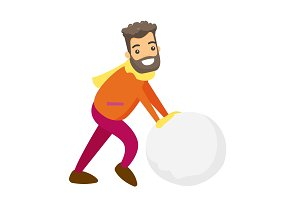 Caucasian man making a big snowball for snowman.