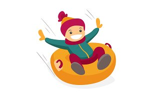 Caucasian boy sledding down on snow rubber tube.