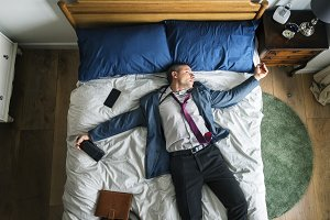 Business man falling asleep on bed