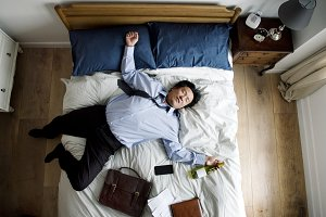 Businessman is falling asleep on bed