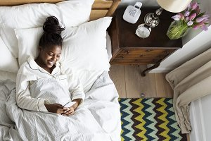 Smiling African woman on bed