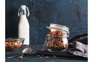 Homemade granola in glass jar on dark table