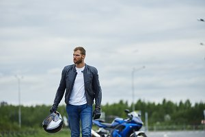 bearded motorcyclist in blue jeans