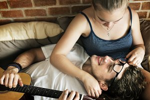 Couple on bed man playing guitar