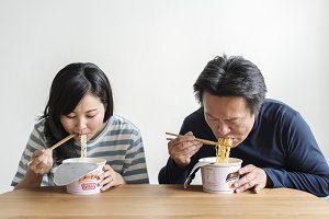 Asian couple eating instant noodles