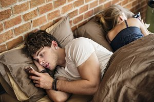 Couple using mobile phone on bed