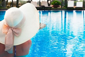 Woman  with hat  from back in  swimming pool