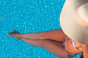 Lady in hat laying in the blue water