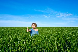 Woman showing thumbs up gesture in green field