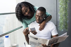 Black couple using mobile phone