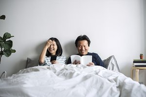 Asian couple relax on bed together