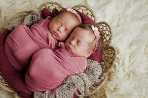twins sisters newborn in the winding and in a basket