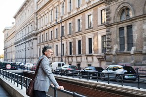 Mature businessman standing in a city.