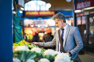 Mature businessman buying vegetables in a city.