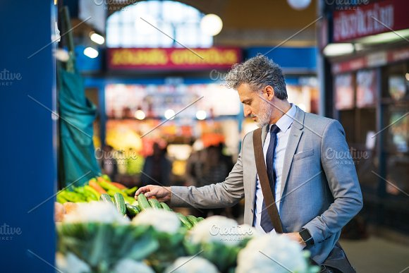 Mature Businessman Buying Vegetables In A City