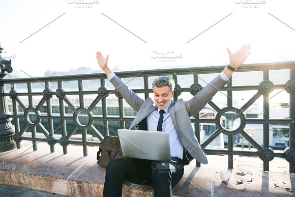 Mature Businessman With A Laptop In A City