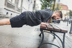 Man doing push-ups on a bench.