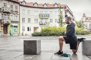 Man streching his legs in the city