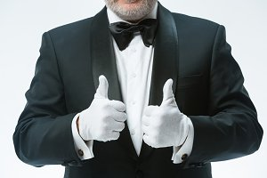 Senior waiter in white gloves
