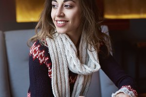 Smiling woman dressed in a sweater and scarf in cafe with cup of coffee