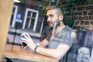 Man in a cafe looking by the window.