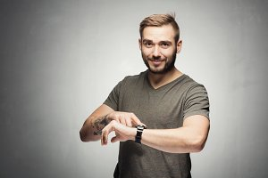 Handsome man pointing at a watch on