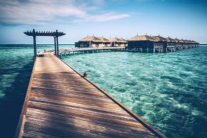 Wooden jetty with arch on a clean tu