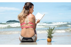 beautiful girl sitting on the beach and reading a book on exotic landscapes and pineapple