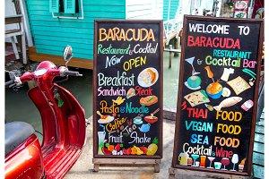 menu on a wooden chalkboard near a restaurant