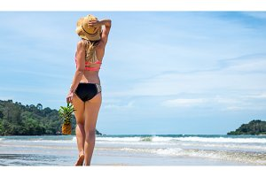 beautiful girl with a straw hat and a walking pineapple on an exotic beach, good food and rest