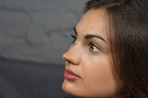 Portrait close-up of a brunette girl with brown eyes looking away