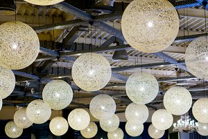 Background of white balls lamps suspended to the ceiling on metal beams