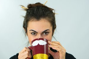 Portrait of a brunette girl holding a funny cup with a white mustache