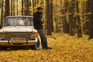 Smiling bearded man with a tattoo stands near a retro car in an autumn forest