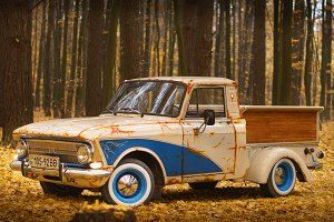 Custom truck creative idea with blue color artificial rust and wooden luggage retro cars in a fall forest