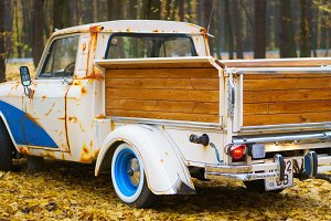 Retro car Moskvich with wooden customized luggage in the autumn forest