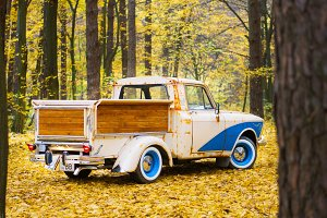 Old Russian car Moskvich with wooden customized luggage in the autumn forest
