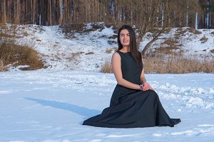 Young brunette caucasian girl smiling in a black dress on the snow