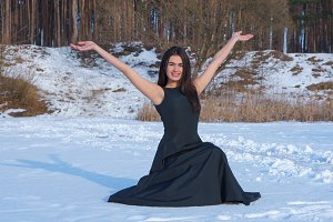 Young brunette girl in a black dress happy smiling her hands up on the snow background