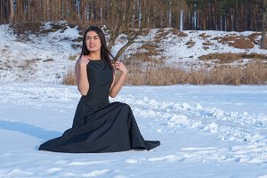 Beautiful brunette girl on the snow-covered lake in a black dress is looking far away