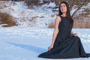 Portrait of a young smiling brunette girl in a black dress on a snow lake