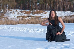 Smiling brunette girl in a black dress in a snowy forest