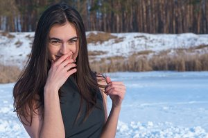 Portrait attractive smiling young brunette girl touches her face with hand on a snowy landscape background