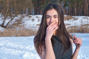 Smiling young girl attractive brunette touches her face with hand on a snowy landscape background