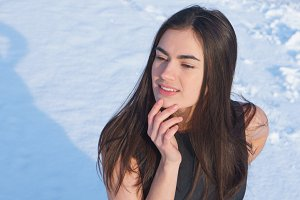 Portrait attractive young brunette girl touches her face with hand on a snowy background