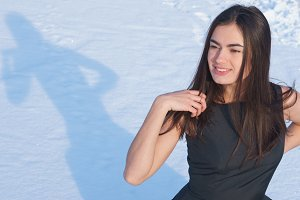 Portrait attractive young brunette girl on a snowy background